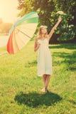 La donna sorridente sceglie il grande o piccolo ombrello dell'arcobaleno all'aperto Fotografia Stock Libera da Diritti