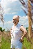 La donna sorridente si leva in piedi sul prato al giorno di estate Immagine Stock Libera da Diritti