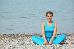 La donna sorridente sta allungando su un litorale del mare Fotografie Stock