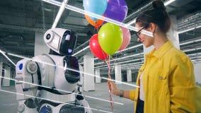La donna sorridente sta dando i palloni ad un cyborg alto video d archivio
