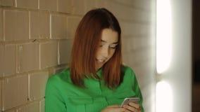 La donna sorridente sta fermandosi accanto alla parete che funziona con mandare un sms di messaggio del cellulare archivi video