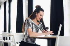 La donna sorridente sta sedendosi ad uno scrittorio con un computer portatile e ad esaminare lo sreen mentre teneva uno smartphon Immagini Stock Libere da Diritti