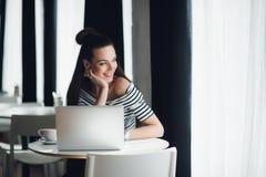 La donna sorridente sta sedendosi ad uno scrittorio con un computer portatile e sta guardando attraverso la finestra meditatament Immagini Stock Libere da Diritti