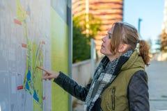 La donna sorridente sta studiando la mappa di itinerario immagine stock libera da diritti