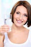 La donna sorridente tiene un vetro di acque pulite immagine stock libera da diritti