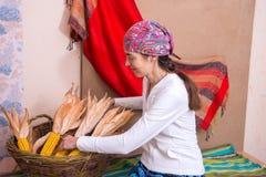 La donna sorridente utilizza il cereale in un canestro del villaggio come uno dei elemen Fotografie Stock