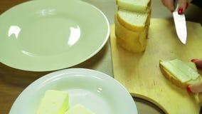 La donna spalma il burro su pane per le canape stock footage