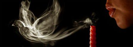 La donna spegne una candela immagini stock