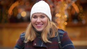 La donna spensierata felice con capelli biondi invia un bacio dell'aria sopra il fondo delle luci di Natale Bella ragazza che ind stock footage