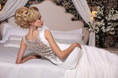 La donna splendida con capelli biondi indossa il vestito da sposa lussuoso ed il gioiello Fotografie Stock Libere da Diritti