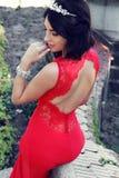 La donna splendida con capelli scuri indossa il vestito lussuoso ed il gioiello Fotografia Stock