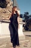 La donna splendida con capelli scuri porta il vestito lussuoso Fotografia Stock