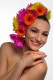 La donna splendida con la gerbera una la sua testa sorride Immagini Stock Libere da Diritti