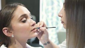 La donna splendida sta sedendosi allo studio cosmetico con trucco dell'eleganza stock footage