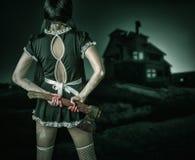 La donna sporca sta indietro tenente un'ascia sanguinosa Immagini Stock Libere da Diritti