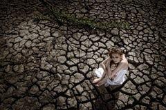 La donna sporca triste è al deserto incrinato della terra Fotografia Stock