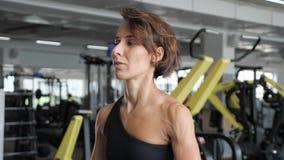 La donna sportiva in abiti sportivi spande le sue mani al lato con le teste di legno in palestra archivi video
