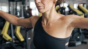 La donna sportiva in abiti sportivi spande le sue mani al lato con le teste di legno in palestra stock footage