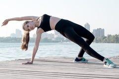 La donna sportiva allunga alla posa di yoga durante il outd di allenamento di addestramento Immagine Stock
