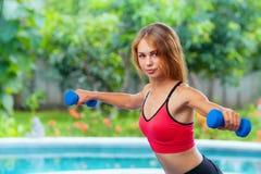 La donna sportiva attiva che fa la mattina si esercita con le teste di legno a casa Fotografia Stock Libera da Diritti