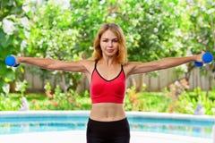 La donna sportiva attiva che fa la mattina si esercita con le teste di legno a casa Immagine Stock Libera da Diritti