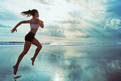 La donna sportiva attiva funziona lungo la spiaggia dell'oceano del tramonto Mette in mostra il fondo Fotografie Stock Libere da Diritti