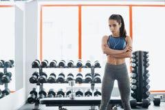 La donna sportiva che sta con le armi ha attraversato nella palestra di forma fisica fotografia stock libera da diritti