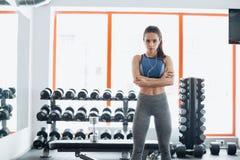La donna sportiva che sta con le armi ha attraversato nella palestra di forma fisica fotografia stock