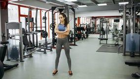 La donna sportiva che sta con le armi ha attraversato nella palestra di forma fisica immagine stock