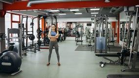 La donna sportiva che sta con le armi ha attraversato nella palestra di forma fisica fotografie stock libere da diritti