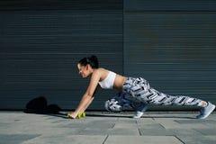 La donna sportiva con la figura perfetta e le natiche modellano l'allungamento delle gambe con le teste di legno vicino alla pare Immagini Stock