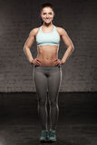 La donna sportiva con un bello sorriso, femmina di forma fisica con l'ente muscolare, fa il suo allenamento, abdominals Immagine Stock