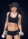 La donna sportiva di forma fisica nell'addestramento che pompa su muscles con le teste di legno Fotografie Stock