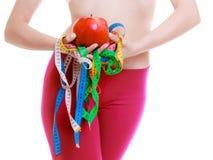 La donna sportiva di misura con la misura lega la frutta con un nastro. Tempo per il dimagramento di dieta. Immagini Stock