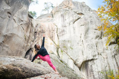 La donna sportiva di misura sta praticando l'yoga sul masso nella natura Fotografia Stock Libera da Diritti
