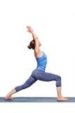 La donna sportiva di yogini di misura pratica il utthita Virabhadras di asana di yoga immagine stock
