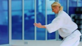 La donna sportiva mostra un trucco di karatè con le mani nella palestra archivi video