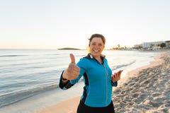 La donna sportiva motivata che fa i pollici aumenta il gesto di successo dopo l'allenamento urbano sulla spiaggia Immagini Stock Libere da Diritti