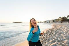 La donna sportiva motivata che fa i pollici aumenta il gesto di successo dopo l'allenamento urbano sulla spiaggia Immagine Stock