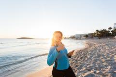 La donna sportiva motivata che fa i pollici aumenta il gesto di successo dopo l'allenamento urbano sulla spiaggia Fotografia Stock