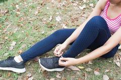 La donna sportiva nell'usura di sport che lega le sue scarpe si prepara per l'allenamento Fotografia Stock Libera da Diritti