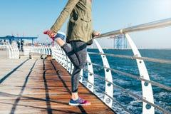La donna sportiva in rivestimento e scarpe da tennis sta allungando le sue gambe sopra Fotografie Stock