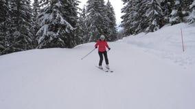 La donna sportiva scia professionale su un pendio della stazione sciistica della montagna stock footage