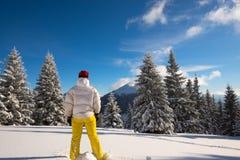 La donna sportiva si rilassa sul prato alpino all'inverno magico Fotografia Stock Libera da Diritti