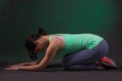 La donna sportiva sorridente si rilassa su un fondo scuro con la lampadina verde Immagini Stock