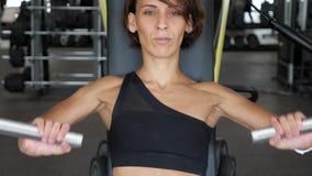 La donna sportiva sta facendo gli esercizi per i muscoli di armi sulla macchina di formazione archivi video