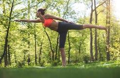 La donna sportiva sta stando nel parco di verde di asana Immagini Stock Libere da Diritti