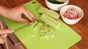 La donna sta affettando il cetriolo fresco nella cucina sulla tavola di legno stock footage