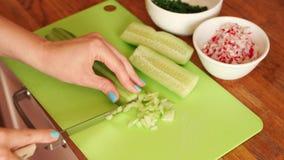 La donna sta affettando il cetriolo fresco nella cucina sulla tavola di legno archivi video