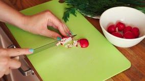 La donna sta affettando il ravanello fresco nella cucina sulla tavola di legno archivi video